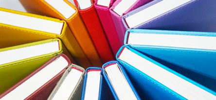 Books with bright covers arranged by their spines in a circle, representing knowledge sharing