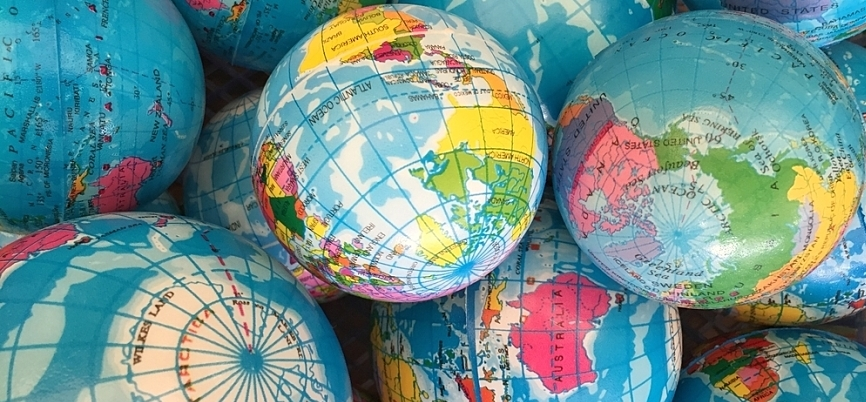 A handful of small globes, representing the challenge of managing remote employees' training
