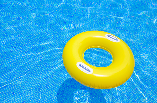 A yellow life raft in bright blue water.