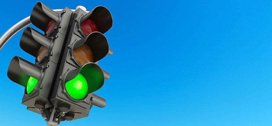 A stoplight on green against a blue background