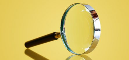 A magnifying glass on a yellow background, representing microlearning