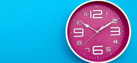 A pink clock on a bright blue background.