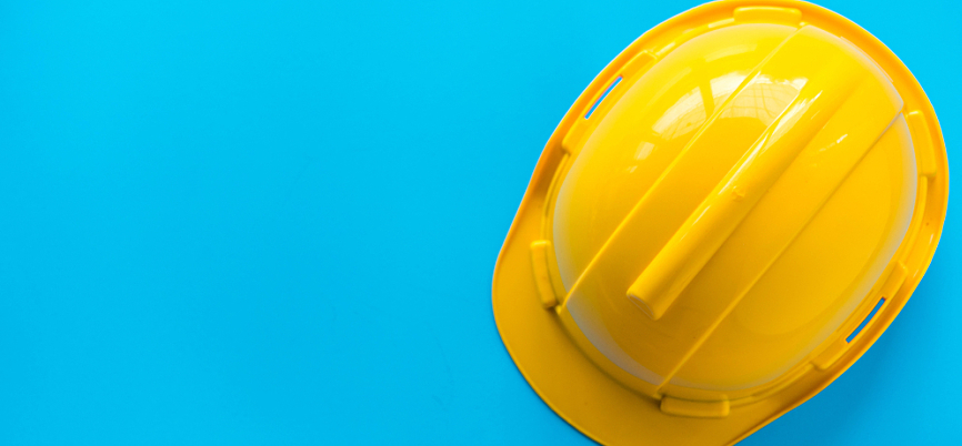 A bright yellow helmet on a bright blue background