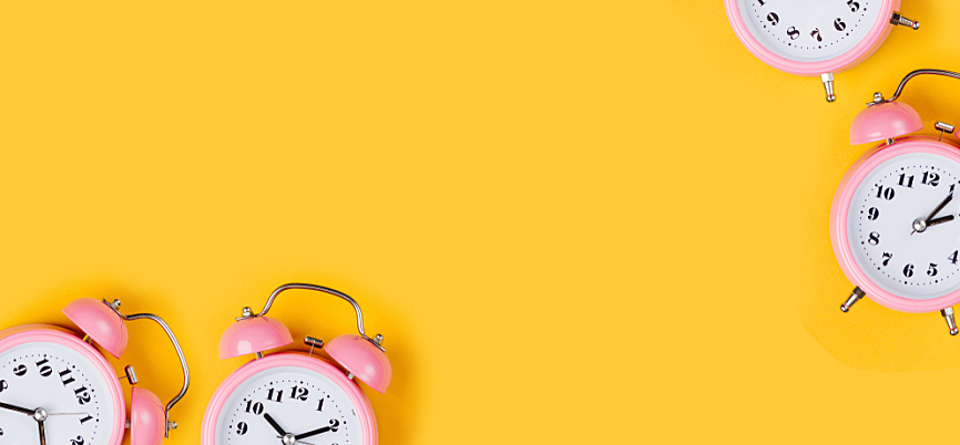 Pink alarm clocks set on a bright yellow background