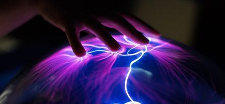 A hand touching a plasma globe